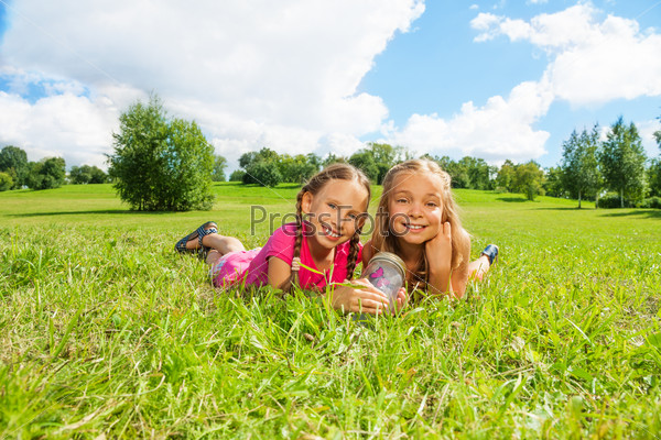 Two girls in the grass with butterfly