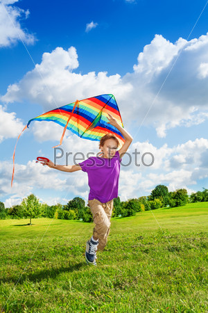 Happy boy running with kite