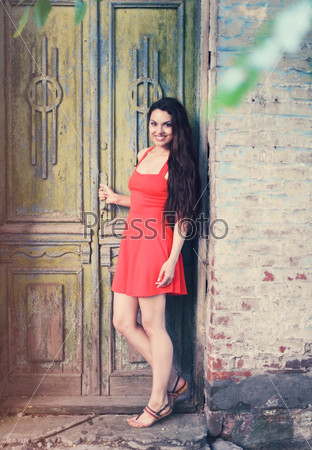 Retro image of cute girl near the old door
