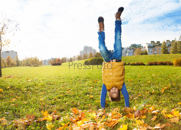Boy stand on hands on the lawn
