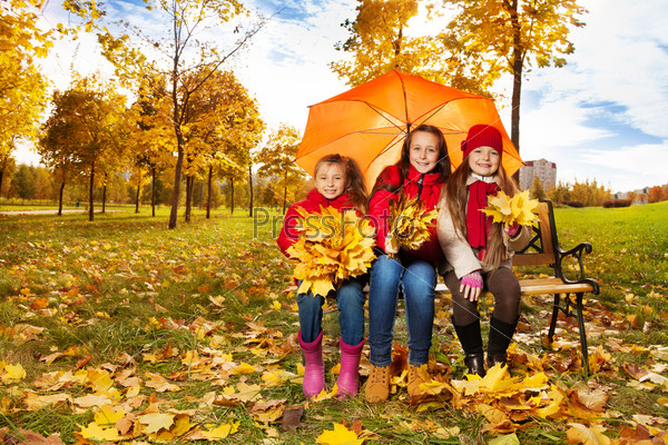 Girls under umbrella in autum park