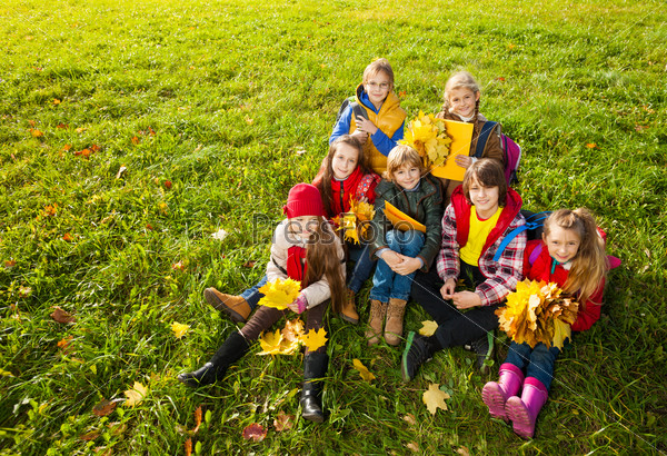 Group of boys and girls on the autumn lawn