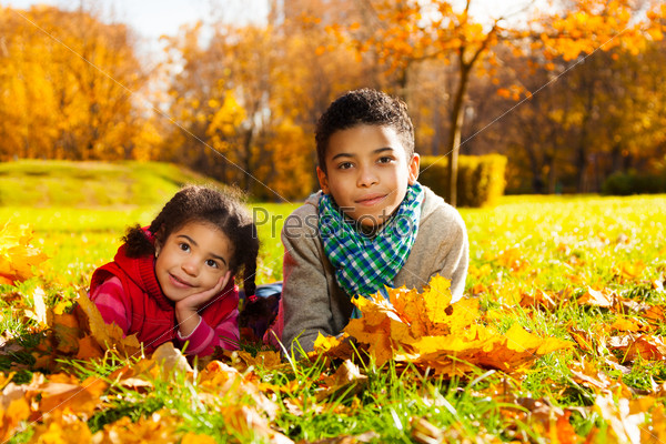 Brother and sister on autumn lawn