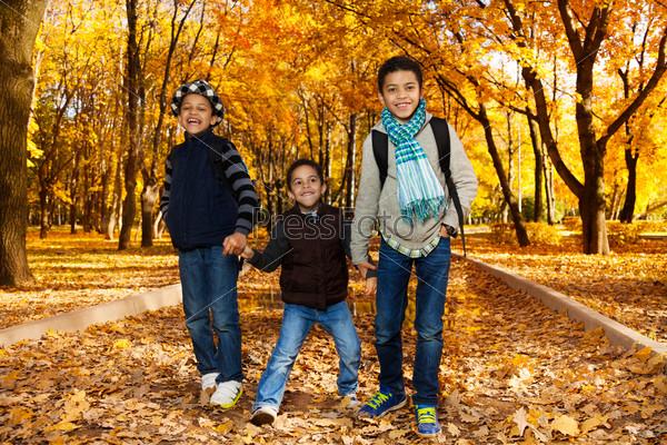 Three kids walk in autumn park