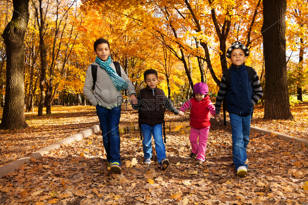 Group of kids walk in autumn park