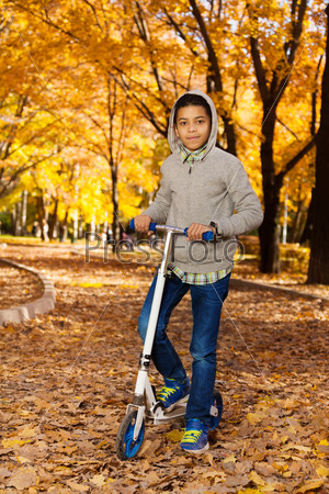 Boy with scooter in October park