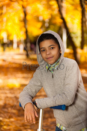 Boy with scooter in autumn park
