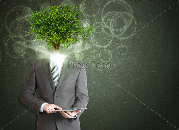Businessman hold tablet pc. Green tree instead his head