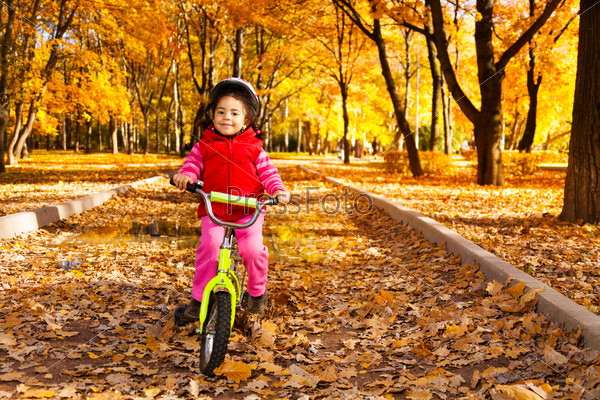 Girl riding bicycle on autumn rode