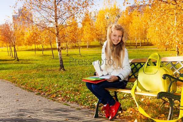 Blond school girl on the bench in the park
