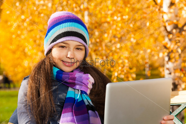 Girl in the autumn park with tablet