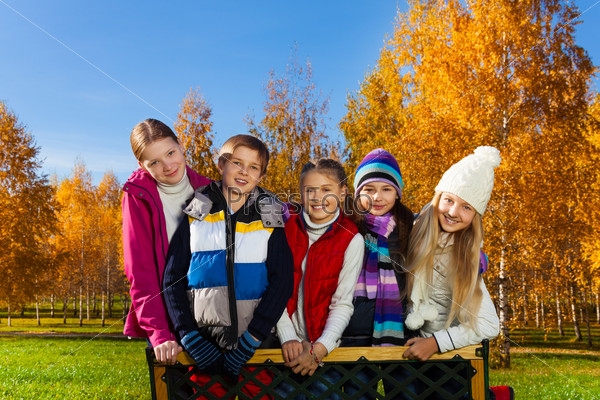 Teen children stand on the bench