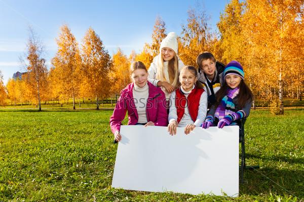 Teen children showing blank placard board