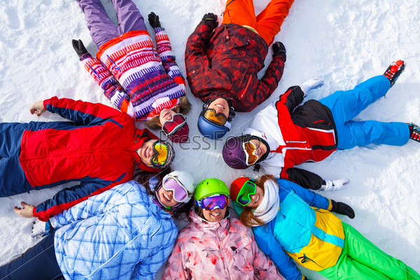 Funny happy snowboarders lying in a circle