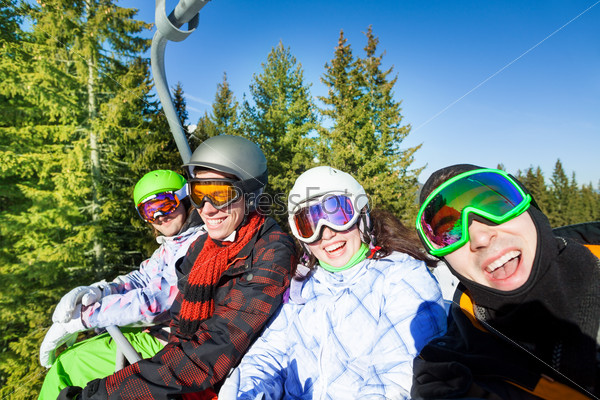 Smiling snowboarders in ski masks on elevator