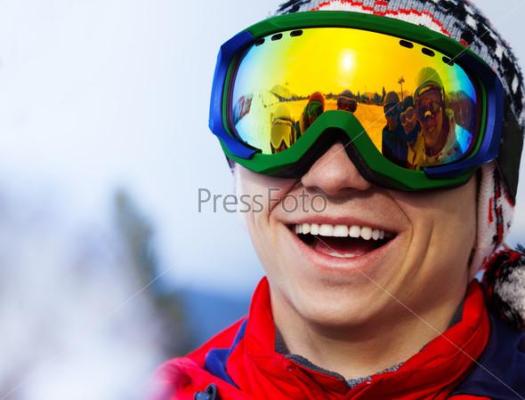 Happy smiling snowboarder in ski mask portrait