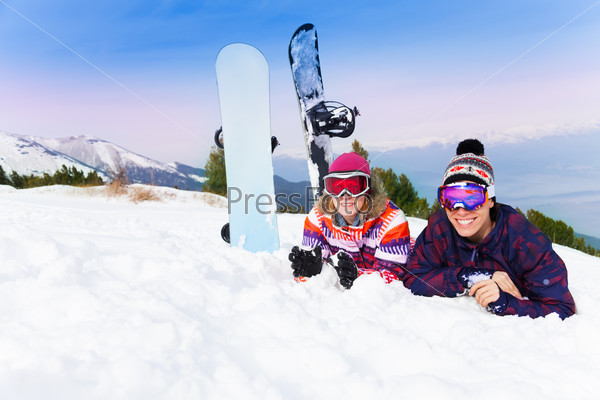 Man and woman in ski masks lying on the snow