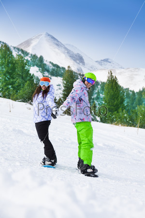 Couple standing on snowboards holding hands