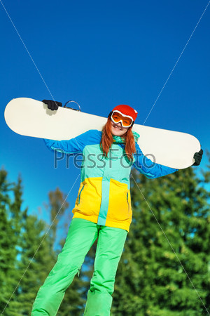 Woman in ski mask standing with snowboard