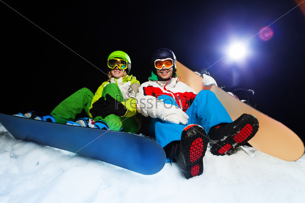 Two smiling snowboarders sitting at night