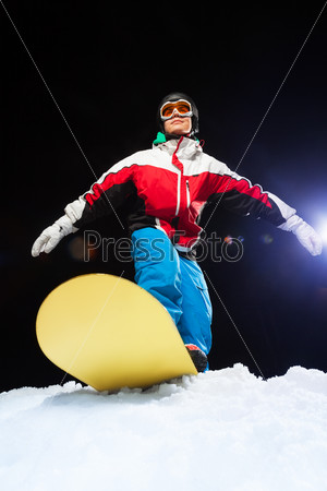 Young snowboarder wearing ski mask ready to slide