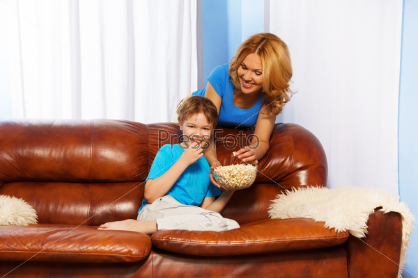 Laughing son eating popcorn and happy mother