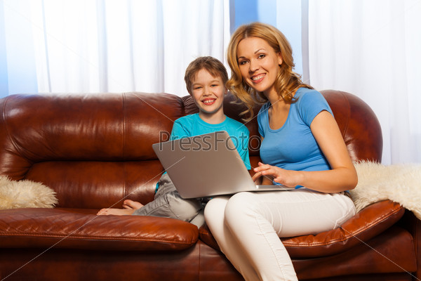 Laughing child and smiling mum with laptop