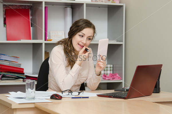 Business girl paints lips with lipstick in the office