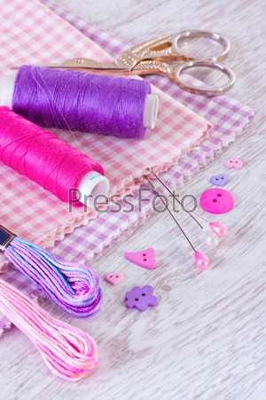Sewing items with a check fabrics, buttons, thread and pins