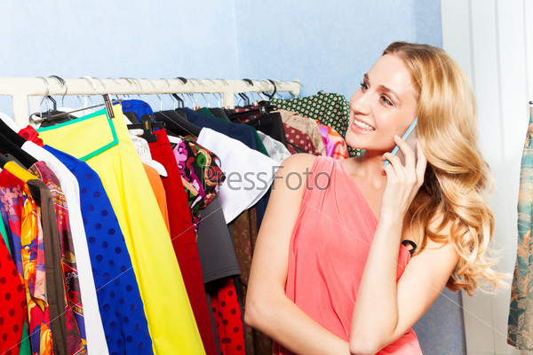 Young woman talking with mobile phone in shop