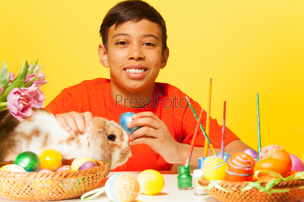 Happy boy with Easter eggs and rabbit on  table