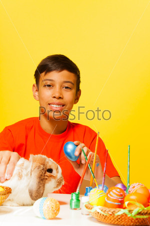 Boy with Easter eggs and cute rabbit on table