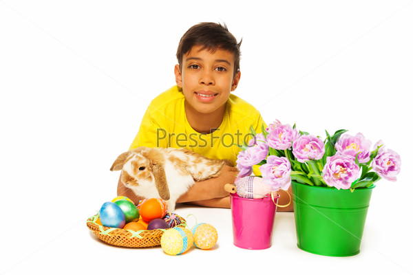 Boy lying and hugging rabbit near Eastern eggs