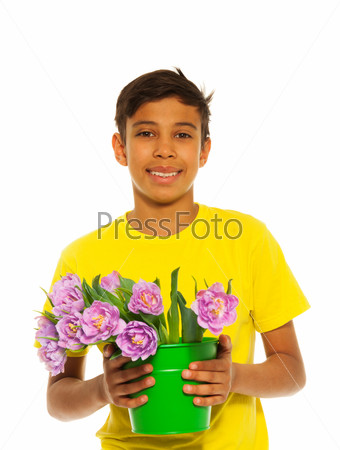 Smiling boy holding pail with pink tulips