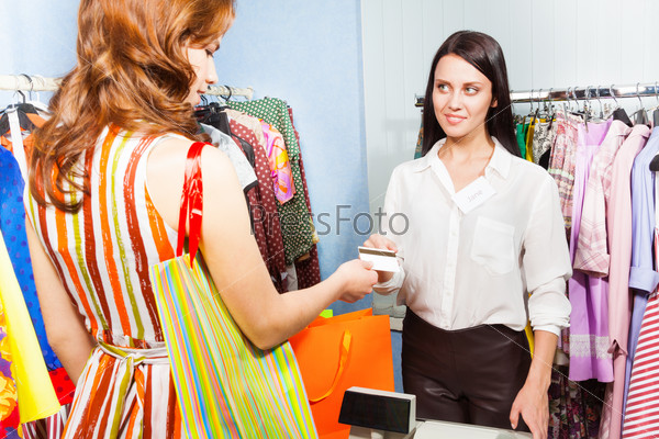 Young woman paying with credit card for  purchase