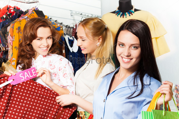 Three young women shopping together in the shop