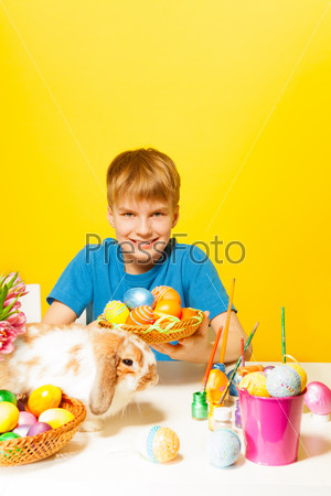 Smiling boy holds plate with Eastern eggs