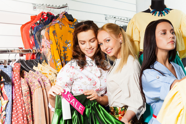 Smiling girls choose clothes during sale