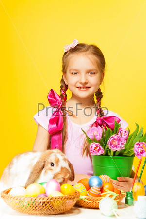 Smiling girl holds pail with pink tulips