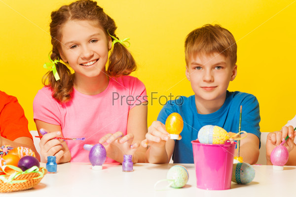 Boy and girl painting Easter eggs at the table