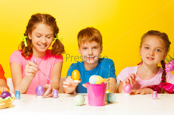 Boy and 2 girls painting Easter eggs at the table