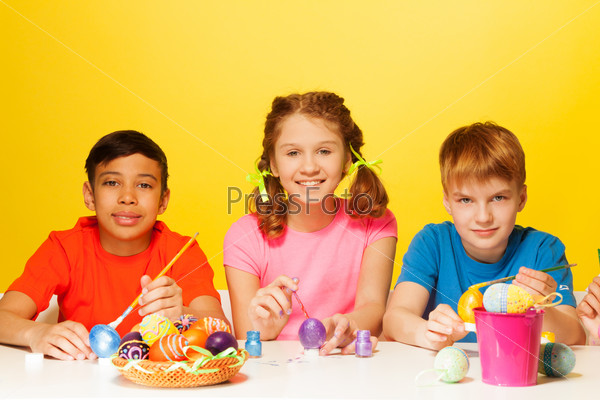 Two boys and girl paint Easter eggs at the table