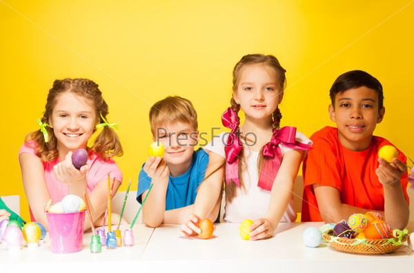 Four children holding Easter eggs at the table