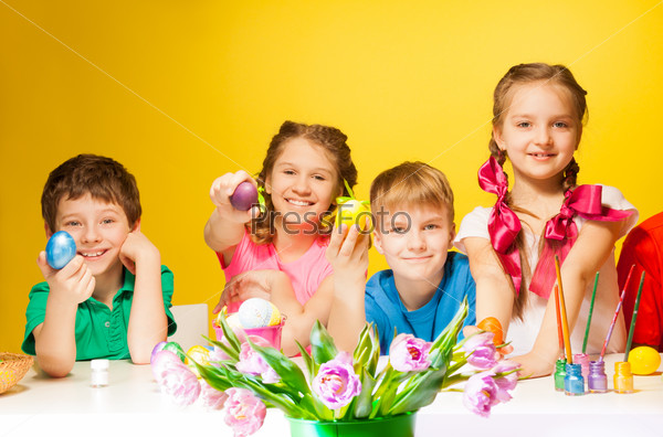 Four children holding coloured Easter eggs
