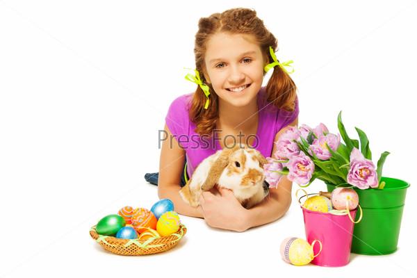 Girl hugging rabbit with Eastern eggs on floor