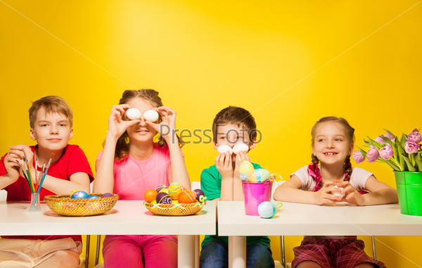 Four children sit at the table with Easter eggs