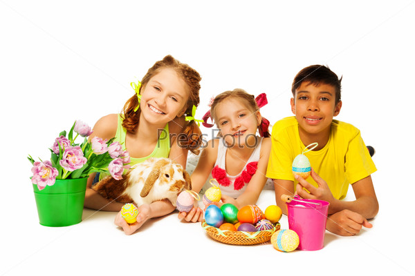 Three cheerful kids together with Eastern eggs