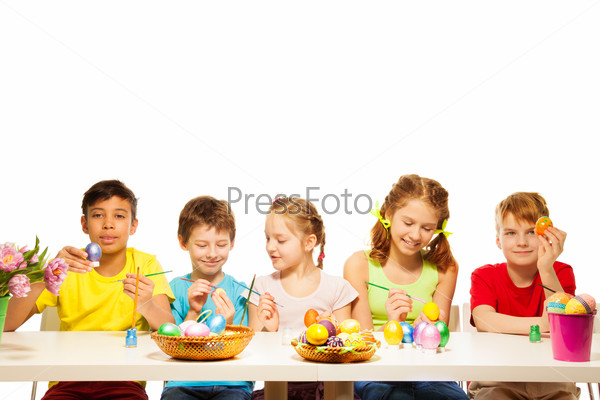 Five kids with colourful Eastern eggs at table