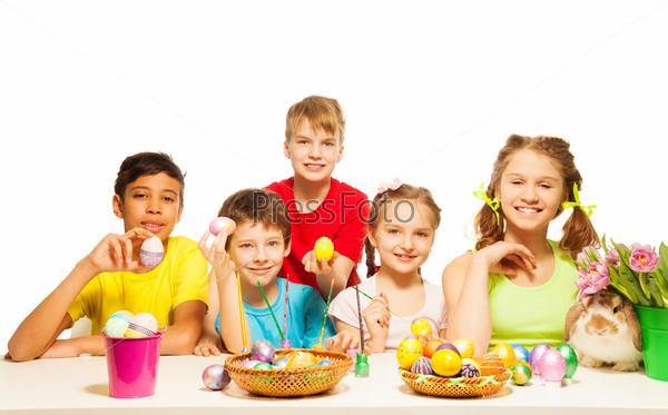 Smiling kids together holding Eastern eggs