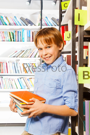 Schoolboy stands and holds books in library